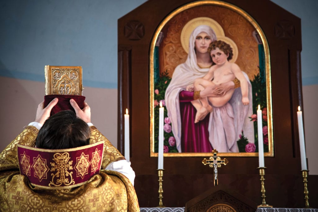 Priest prays at altar with large religious icon in background.