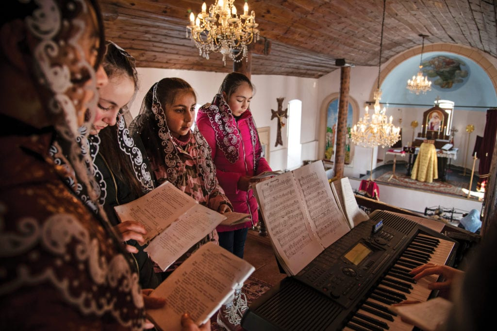 Church choir gathers around keyboard, overlooking the nave below.