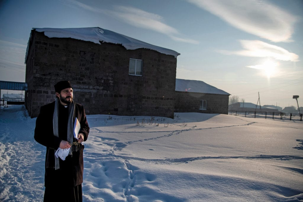 Priest standing in snow on path outside of church.