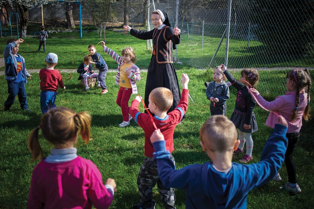 A nun plays outside with a crowd of children.