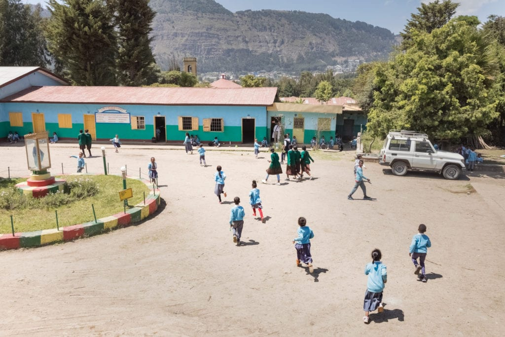 Youth in blue uniforms walk around outside of school buildings.