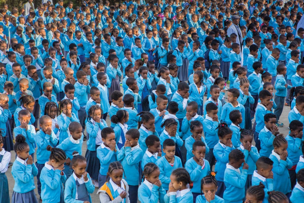 A great many students line up outside in matching blue uniforms.