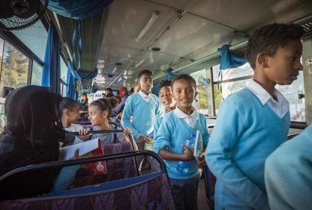 Grinning students walk down the center aisle of a bus.