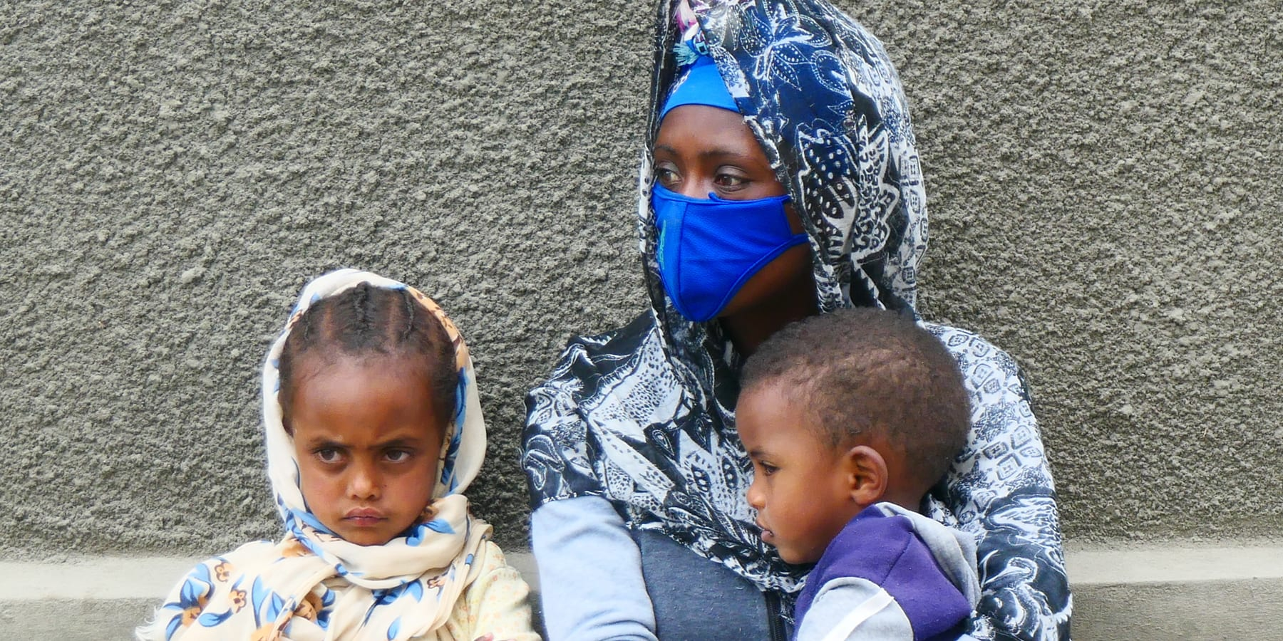 a woman in a mask sits with her two children, one in her lap, against a building wall.