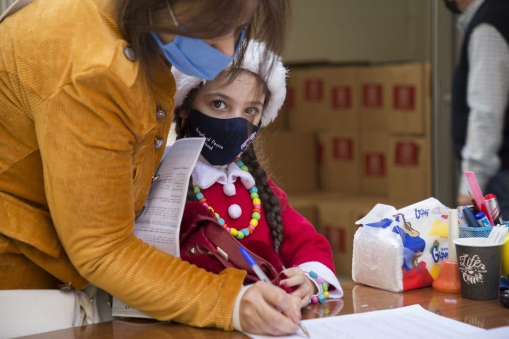 a mother and child sign a paper at a distribution site in Beirut with relief supplies in the background.
