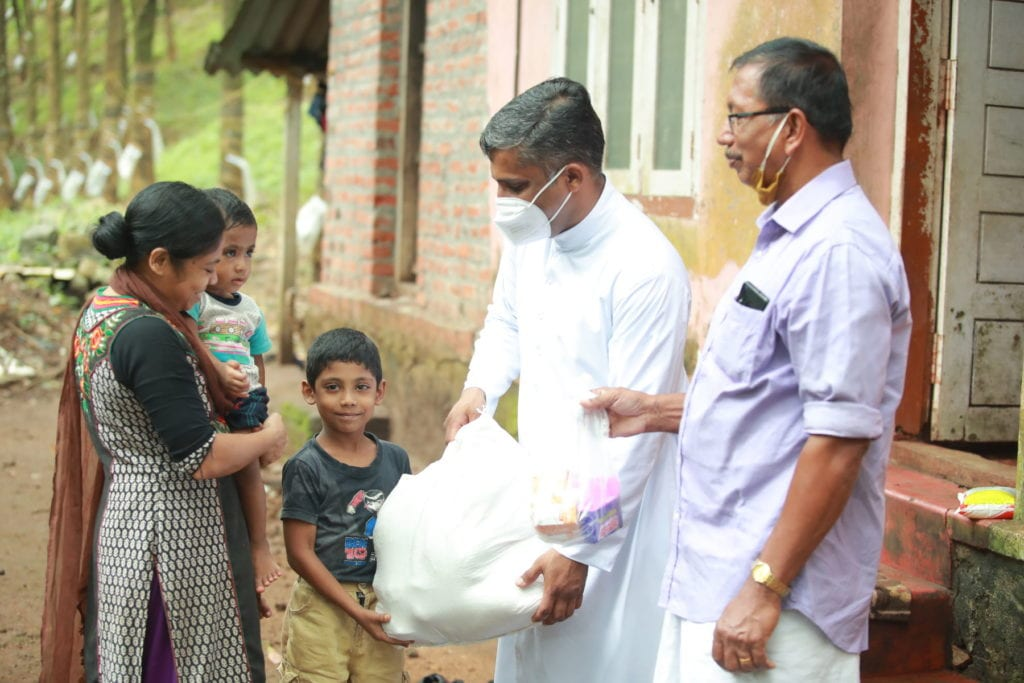 a pair of church workers deliver parcels to a family.