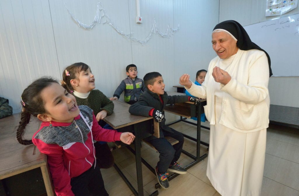 a nun laughs and gestures with both hands while lecturing a classroom of young students in the middle east.