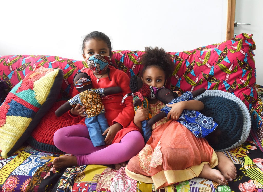 Two 5-year-olds hold dolls as they sit together on a comfy couch.