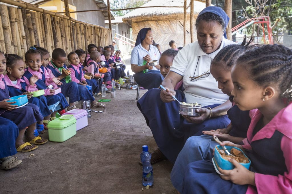 a nun sits with children as they eat lunch.