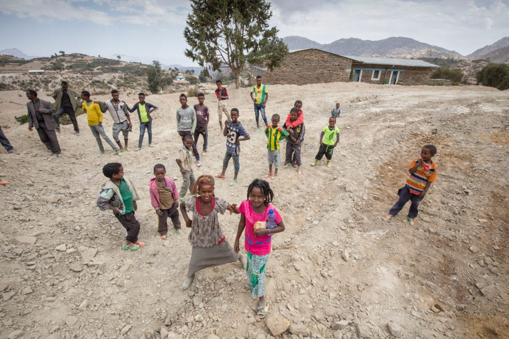 a group of youth stand on a dirt road in northern ethiopia.