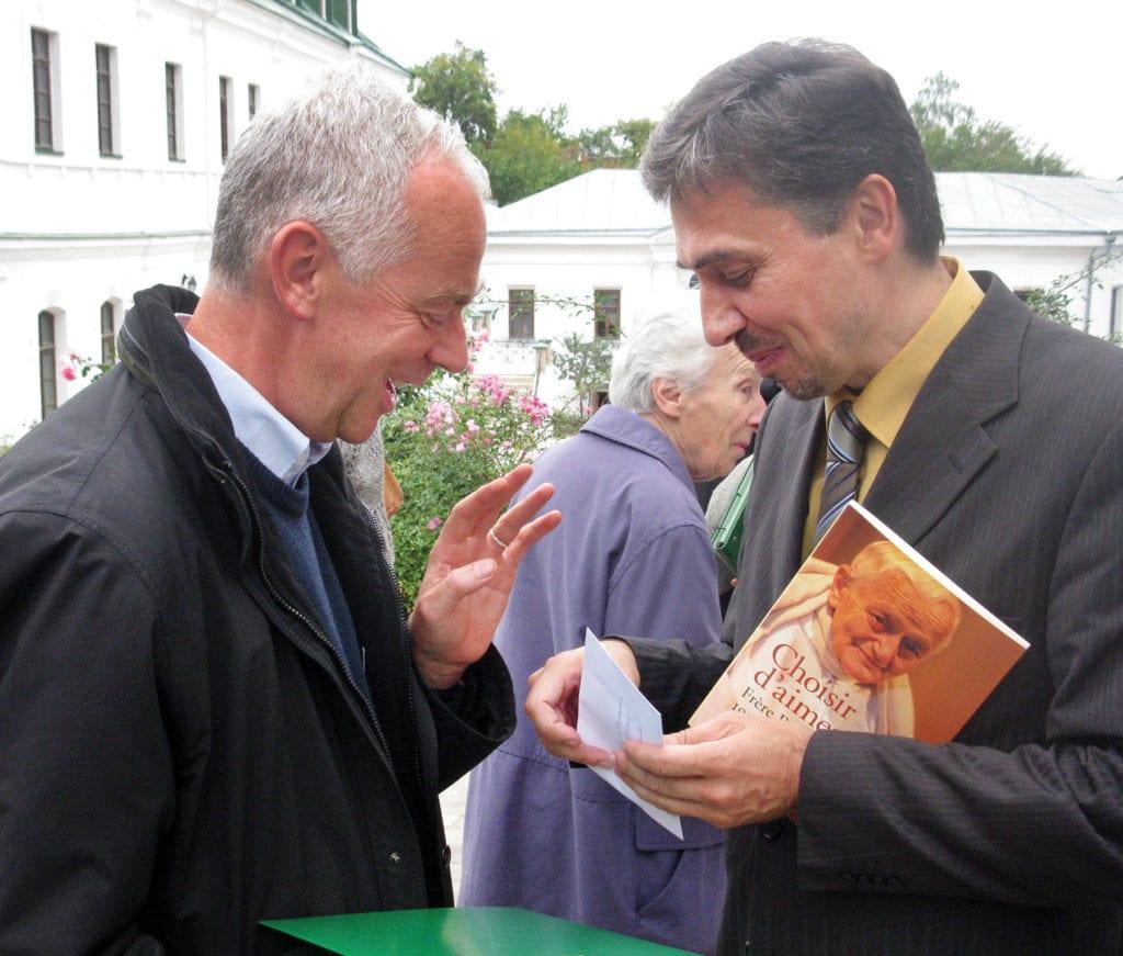 a man offers another man a book.