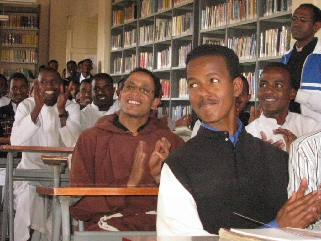 cheerful young men in robes sit at desks in a classroom in Eritrea.