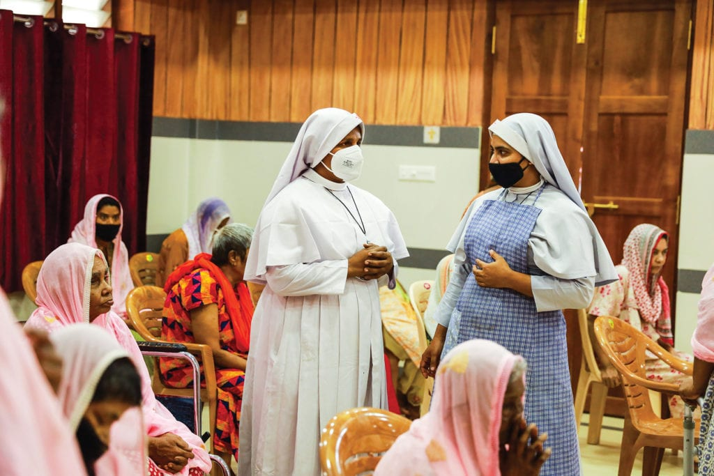two nuns in masks stand in a room with many seated women praying.