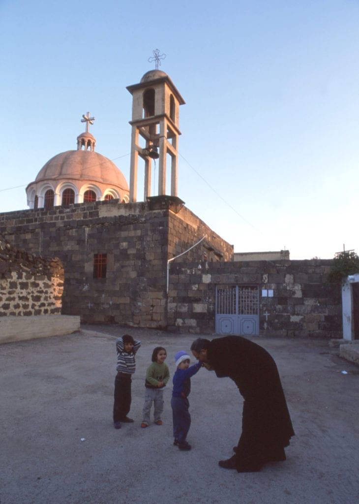 a priest greets three children outside of a church in the middle east.