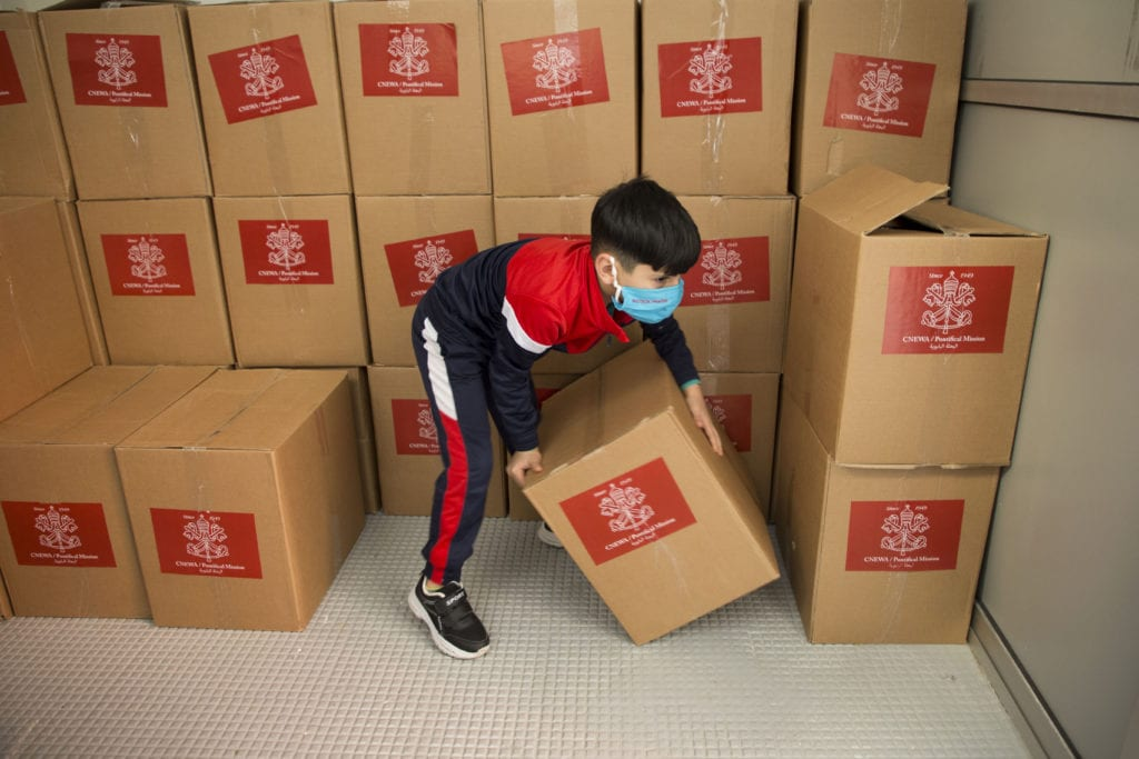 boy handles food boxes in Lebanon