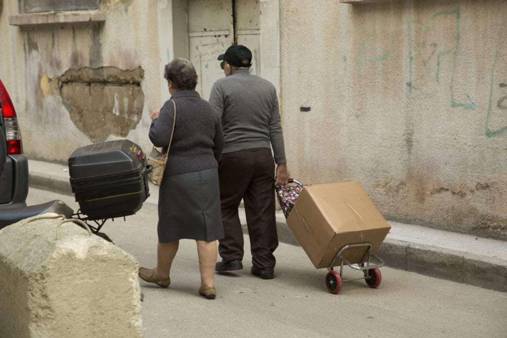 elderly couple walks home with food box in Lebanon