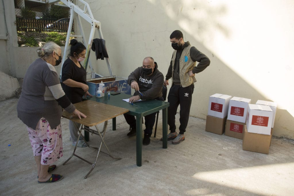 volunteers help to process a request for food at the Palestinian refugee camp in Dbayeh, Lebanon