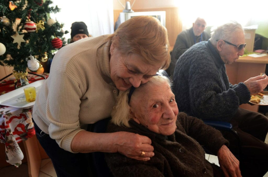 a woman embraces an elderly seated woman.
