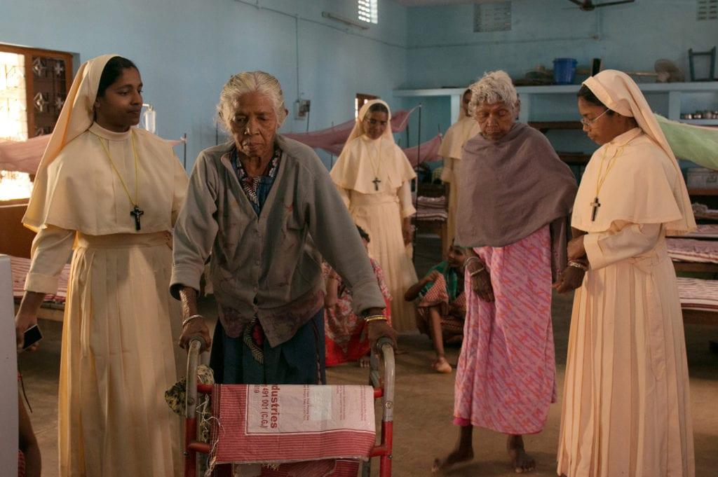 nuns help elderly residents walk.