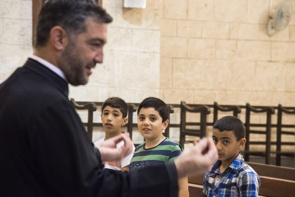 priest talks to children in a church in the middle east.