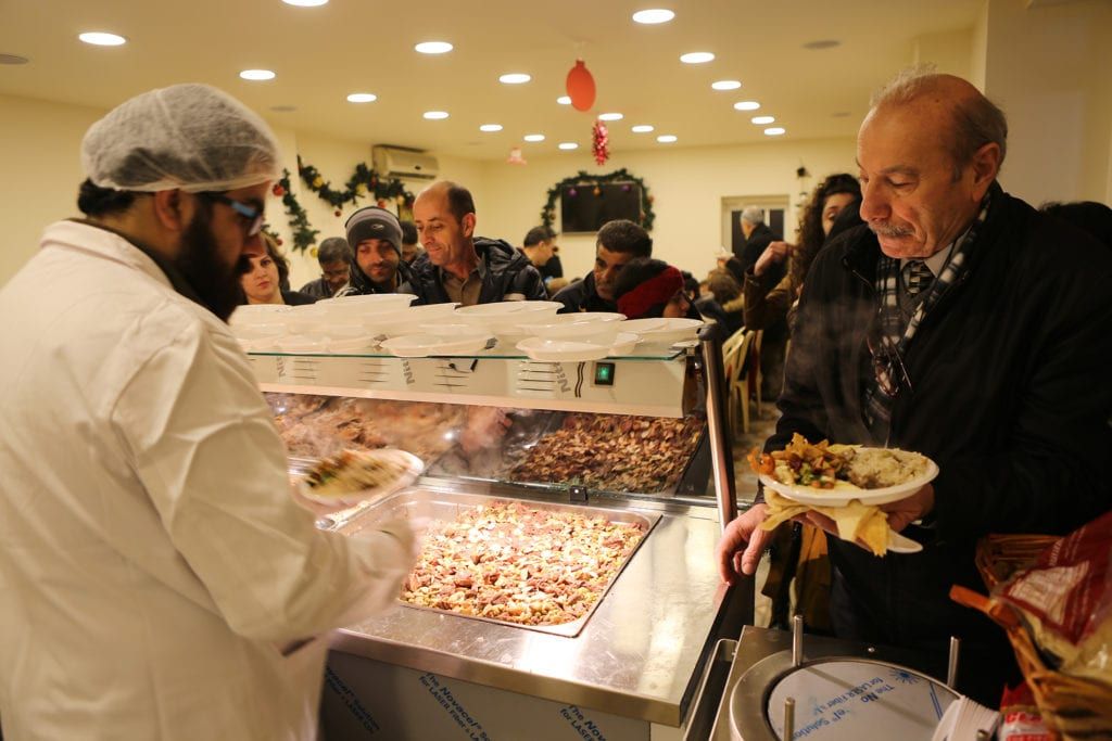 man being served a plate at a food pantry in the middle east.