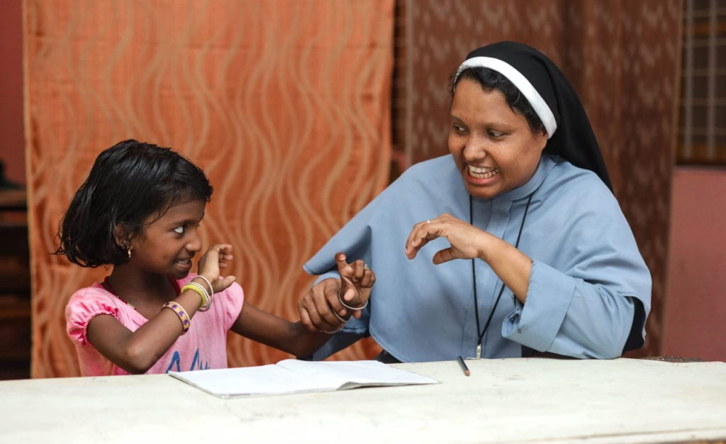 a nun and a young girl, seated at a table, pause from studying to play.