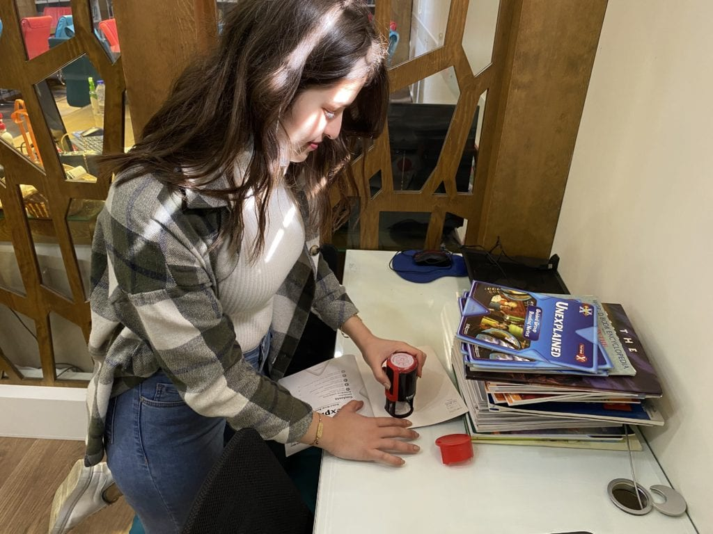 A volunteer prepares English language resources for her tutoring session