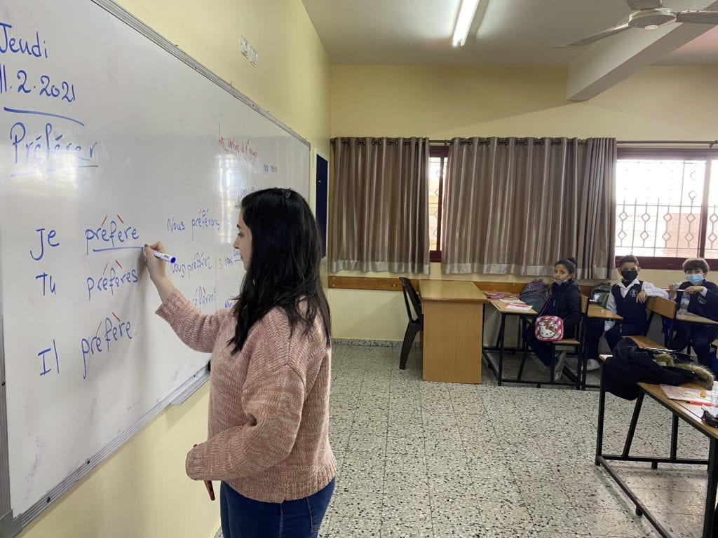 A volunteer teaches a lesson on French verbs at Rosary Sisters School in Gaza