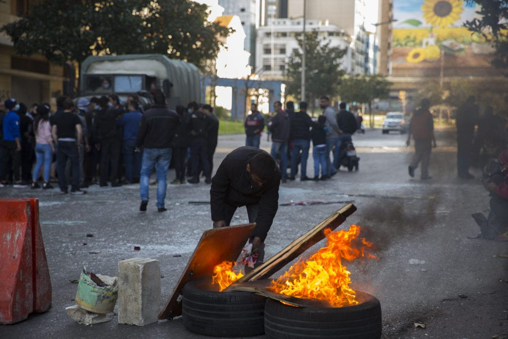 A protest tends to burning tires on a street in Beirut