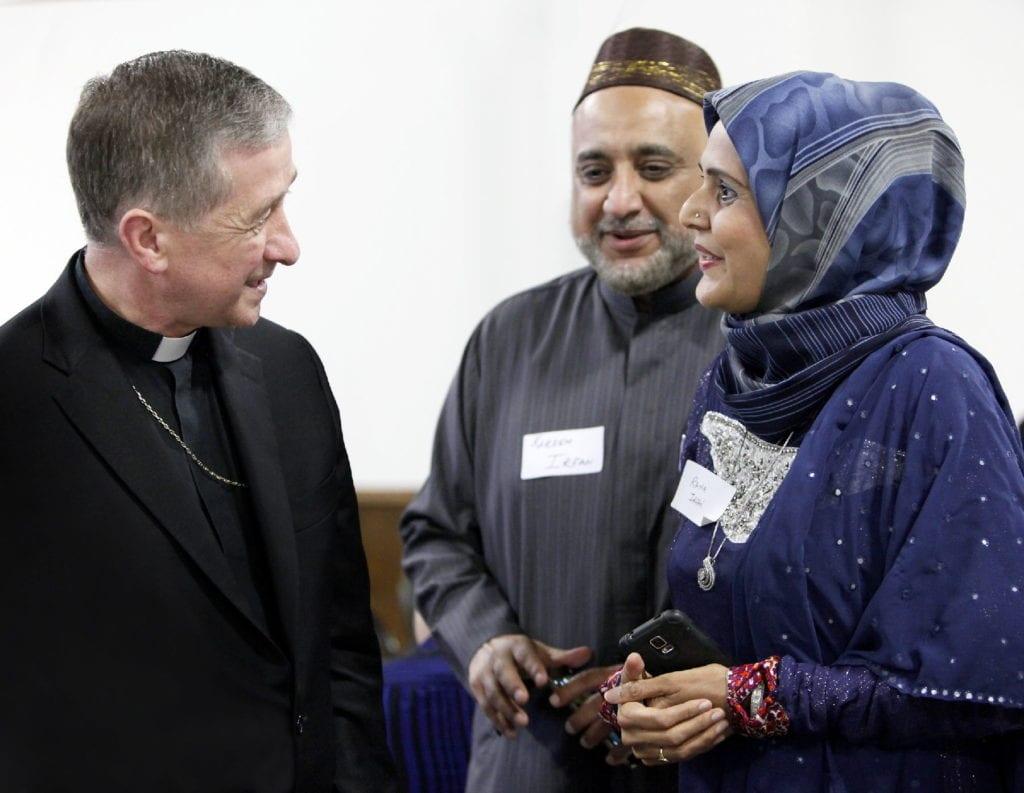 an archbishop greets Muslim colleagues at a Ramadan iftar.