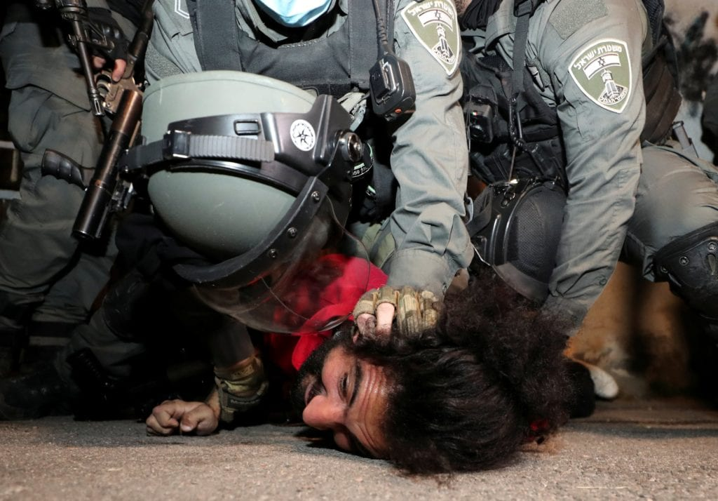 A Palestinian protester is pinned to the ground by Israeli border police.