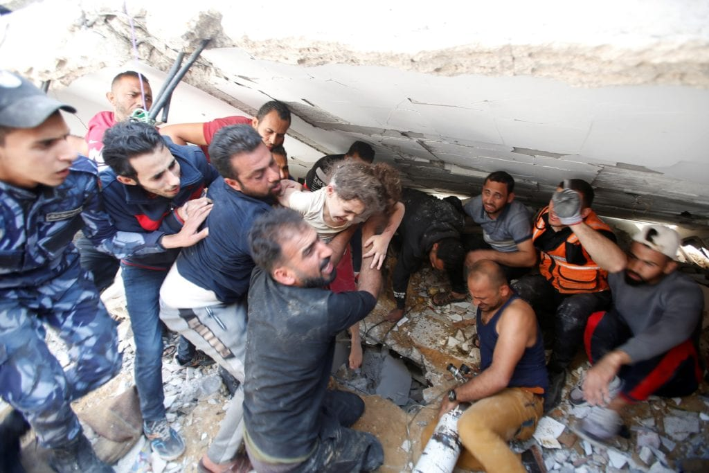 Rescuers carry Suzy Eshkuntana, 6, as they pull her from the rubble of a building at the site of Israeli airstrikes in Gaza City on 16 May.