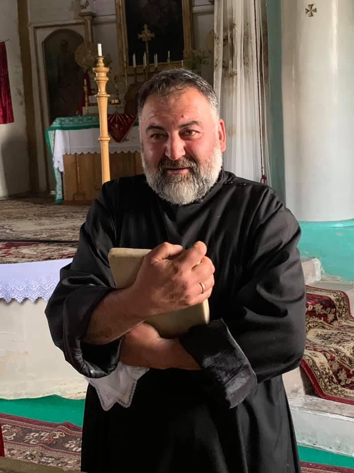 Ter Anton, the pastor of the Armenian Catholic parish in Eshtia, Georgia, clutches onto an altar stone.