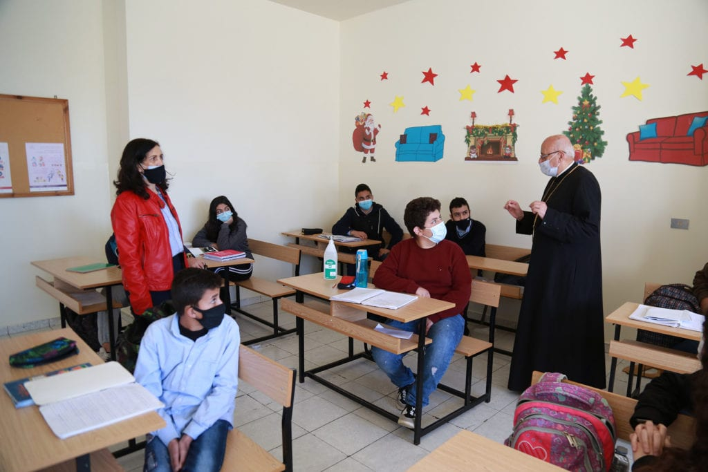 an archbishop in a mask addresses seated students..