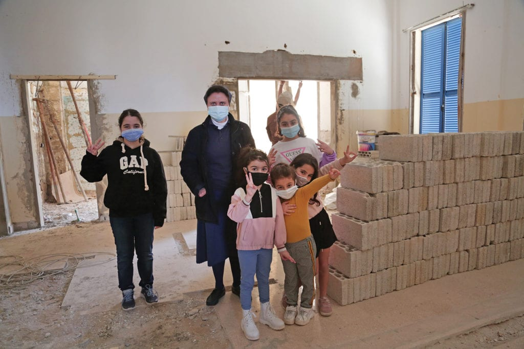 a nun and children look over a partially rebuild classroom.