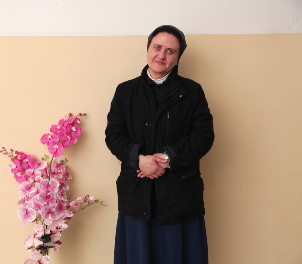 a photo of Sister Marlene Youssef standing beside flowers..