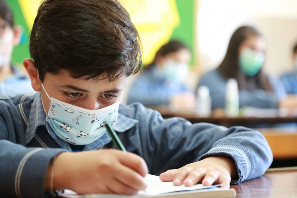 a masked student takes notes at Our Lady of Lebanon School.