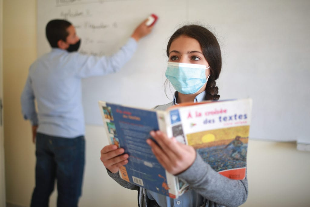 an adolescent girl stands with a text book in class.