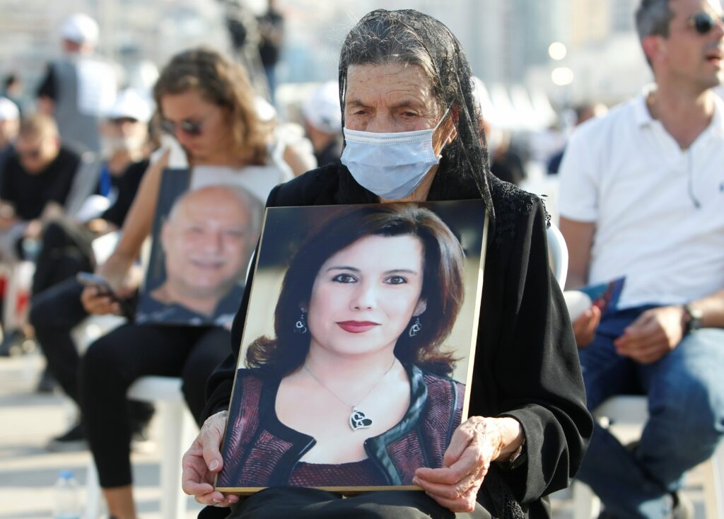 A relative holds a portrait of a victim during a Mass to mark the one-year anniversary of Beirut's port blast on 4 August.