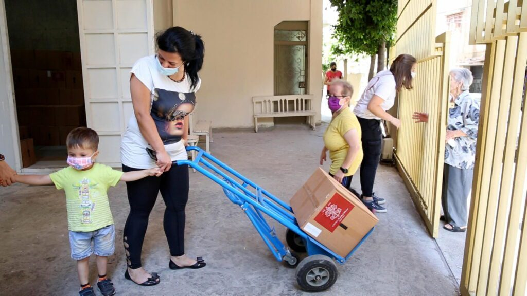 a masked woman and her child wheel a box on a cart.